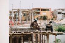 Goree, Senegal - 6 de diciembre de 2017: Dos hombres africanos sentados en un edificio en construcción y mirando hacia otro lado . - foto de stock