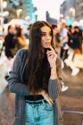 Portrait of delicate brunette girl posing among pedestrians at street — Stock Photo
