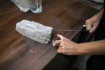 Recortar las manos femeninas cortando trozo de arcilla con cuerda en la mesa de madera - foto de stock