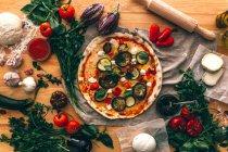 Vista superior de verduras compuestas con pizza cocida e ingredientes en madera . - foto de stock