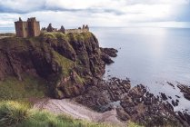 Distant view of Dunnottar Castle standing on cliff on seashore, Scotland. — Stock Photo