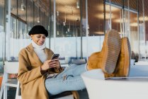Portrait of young woman in warm clothes with feet on cafe table browsing smartphone — Stock Photo