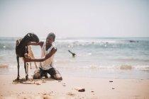 Goree, Senegal- December 6, 2017: Man sitting on sand and washing goat at seaside. — Stock Photo