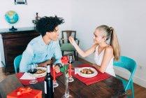 Vista laterale della ragazza bionda che dà cucchiaio con dolcetto al fidanzato a tavola — Foto stock