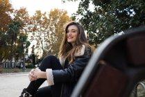 Porträt einer lächelnden brünetten Frau, die auf einer Bank posiert und in die Kamera blickt — Stockfoto