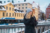 Side view of blonde woman warming hands on bridge in winter city — Stock Photo