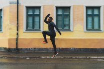 Side view of jogger in warm clothes jumping over asphalt — Stock Photo