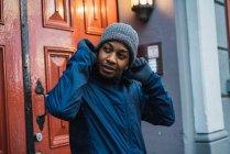 Retrato de homem em pé na porta enquanto coloca o chapéu e olhando para longe — Fotografia de Stock