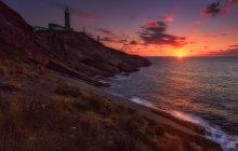 Vue panoramique jusqu'au bord de l'océan dans la lumière du coucher du soleil au bord de mer — Photo de stock
