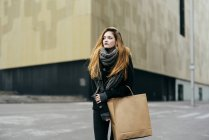 Portrait of young woman with paper hand bag posing on street — Stock Photo