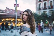 Чувственный женщина в платье, глядя через плечо на камеру — стоковое фото