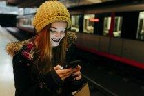Donna sorridente che chiacchiera su smartphone in metropolitana — Foto stock