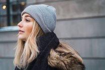 Vista lateral de la sensual mujer rubia con sombrero gris posando en la calle nevada - foto de stock