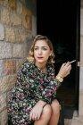 Портрет задумчивой женщины, сидящей на крыльце и курящей сигарету . — стоковое фото