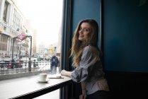 Молодая красивая женщина сидит в кафе и смотрит через плечо на камеру — стоковое фото