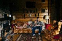 Faire place à l'homme et à la femme allongés sur le canapé à la maison . — Photo de stock