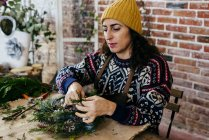 Portrait of woman in hat and sweater sitting at table in atelier and creating Christmas wreath. — Stock Photo