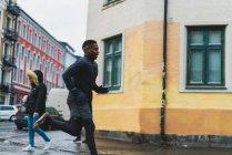 Vue latérale de l'homme sportive en cours d'exécution sur scène de rue — Photo de stock
