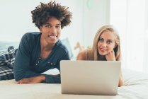 Front view of interracial couple lying on bed with laptop and looking at camera — Stock Photo