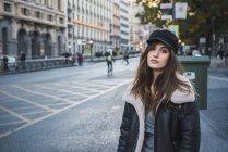 Mulher em boné elegante posando na rua e olhando para a câmera — Fotografia de Stock