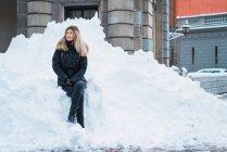 Молодая красивая женщина в непринужденной теплой одежде сидит на куче снег на улице и глядя — стоковое фото