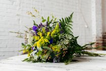 Chiuda sulla vista del bouquet sulla priorità bassa del muro di mattoni bianco — Foto stock