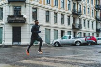 Side view of athletic jogger running on street — Stock Photo