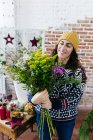 Smiling woman in knitted sweater and hat arranging flowers — Stock Photo