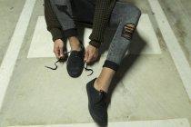 Обтинання чоловіки, пов'язуючи шнурки на асфальт, підставі. — стокове фото