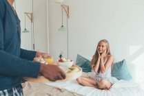 Crop male hands holding tray with breakfast in front of surprised blonde in bed — Stock Photo