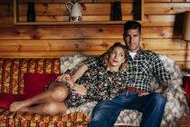 Vue de face du couple embrassant relaxant sur le canapé — Photo de stock