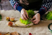 Crop hands creating beautiful flower composition on linen fabric. — Stock Photo