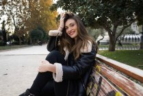 Cheerful young brunette woman sitting on bench and holding head in urban park. — Stock Photo