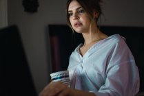 Portrait of woman in white shirt holding cup and using laptop — Stock Photo