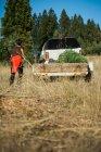 Visão traseira do menino correndo para o carro com reboque e abetos . — Fotografia de Stock