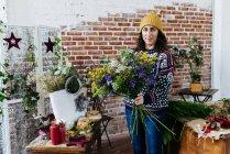 Портрет женщины в вязаный свитер, позируя с довольно букет — стоковое фото