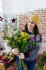 Porträt der lächelnde Frau arrangieren Blumen auf Blumen atelier — Stockfoto