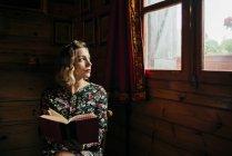 Retrato de um sonho mulher olhando pra janela ao ler o livro em casa. — Fotografia de Stock