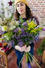 Portrait of cheerful woman holding bouquet in hands — Stock Photo