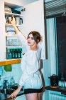 Mulher tomando panela de cima das prateleiras da cozinha e olhando sobre o ombro na câmera — Fotografia de Stock
