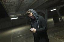 Портрет людина в чорний балахон перегляду смартфон на паркування — стокове фото