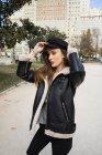 Portrait of stylish brunette woman putting on cap at park — Stock Photo