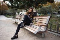 Портрет стильний брюнетка жінка, сидячи на лавці в міський парк — стокове фото