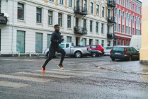 Side view of athletic man running on city street — Stock Photo