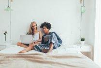 Porträt der schönen interracial paar liegend mit Computer und Tablet im Bett — Stockfoto