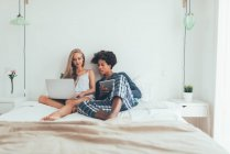 Portrait of beautiful interracial couple lying with computer and tablet in bed — Stock Photo