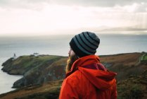 Side view of bearded man standing at coastal hills and admiring seascape — Stock Photo