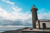 Exterior view of coastal lighthouse over seascape and cloudy sky on background — Stock Photo