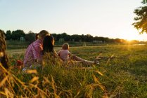 Side view of happy lesbian family with child lying at sunlit park lawn — Stock Photo