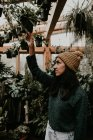 Side view of woman looking plants in greenhouse — Stock Photo